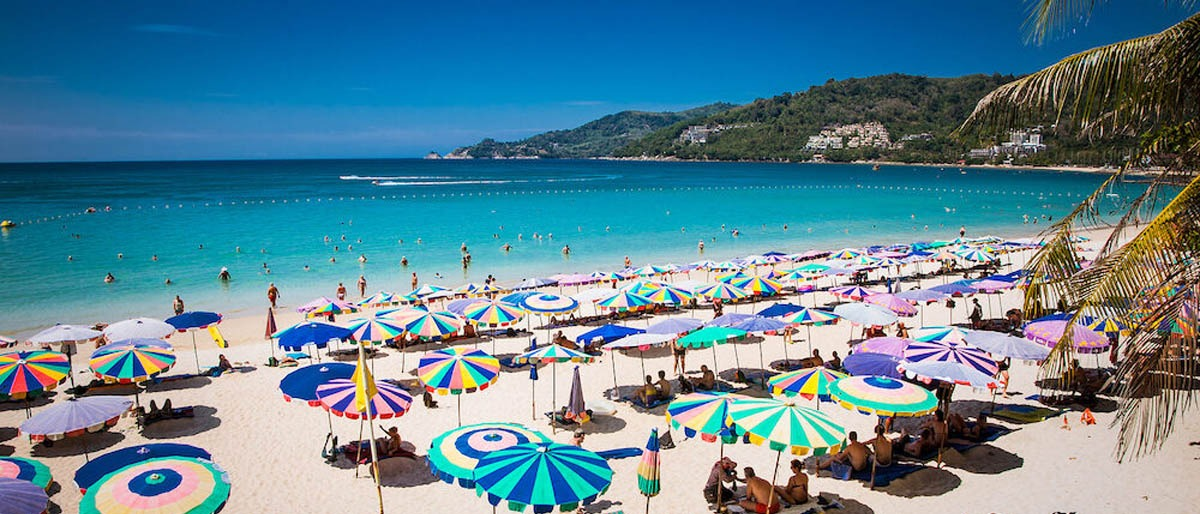 Patong Beach with rows of umbrellas and deck chairs