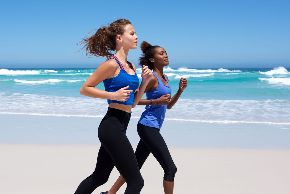Two ladies jogging along the beach