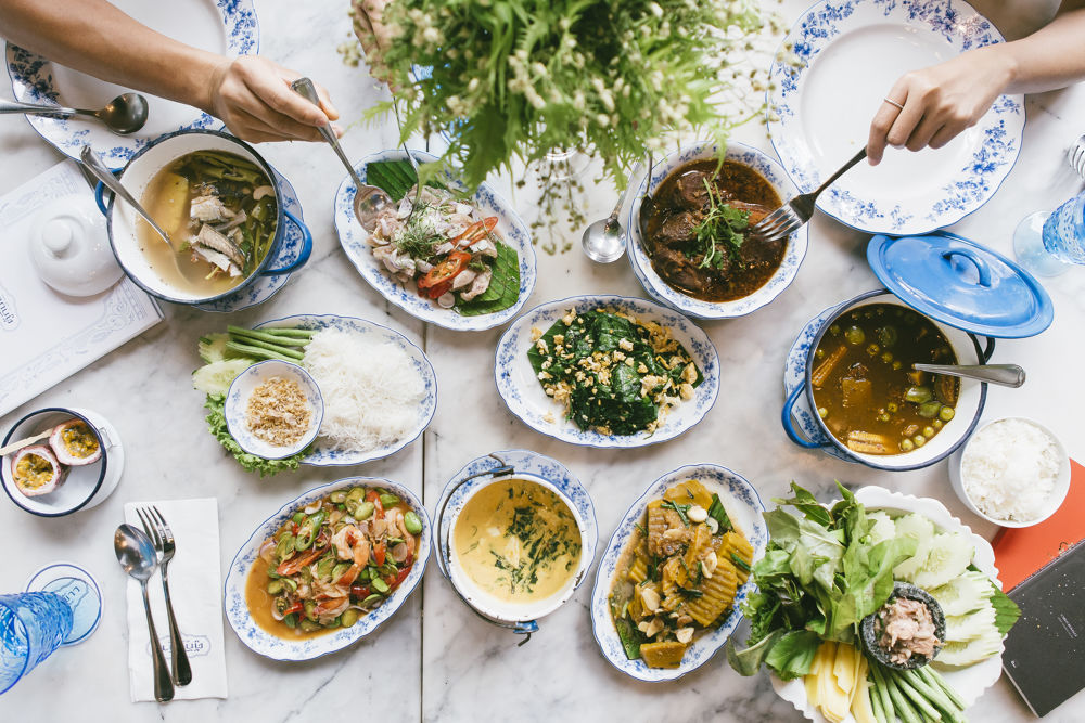 A table with many Thai dishes laid out