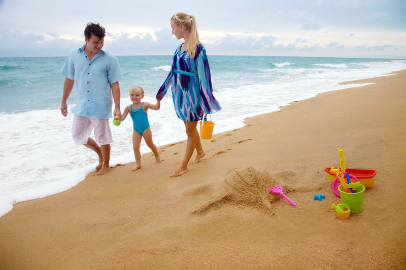 Couple with small child walking along the beach