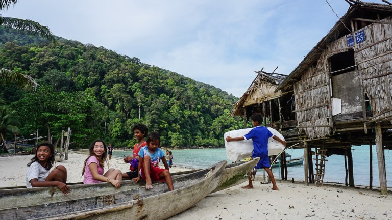 Some sea gypsy kids playing in a wooden boat on the beach