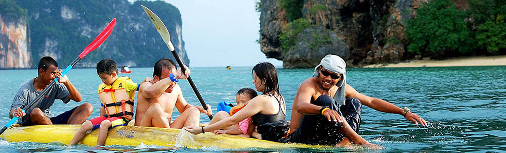 A family being paddled in a sea kayak by their guide