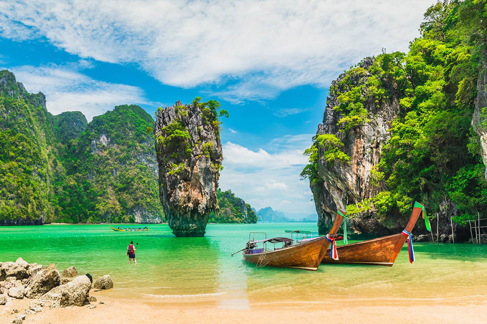 A couple of longtail boats anchored off a beach at James Bond Island