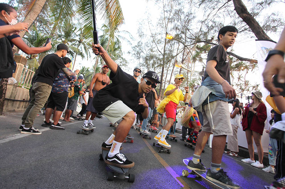 Spectators watching a skating event on the beach road in Kata
