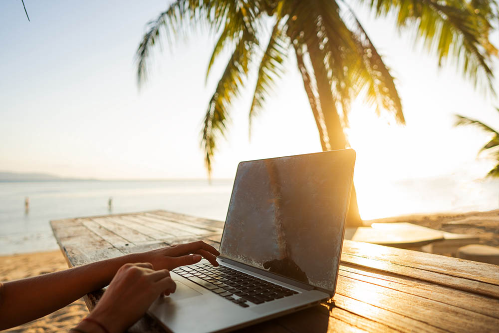 Someone working a laptop on a table beside a beach