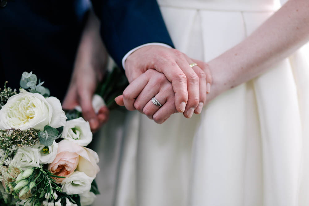 Couple holding hands at a wedding
