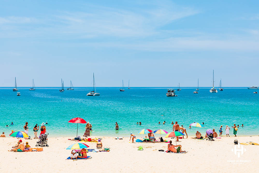 Nai Harn Beach with sunbathers and yachts offshore